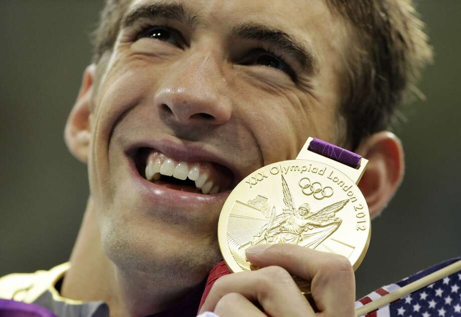 United States' Michael Phelps poses with his gold medal for the men's 4x200-meter freestyle relay swimming final at the Aquatics Centre in the Olympic Park during the 2012 Summer Olympics in London, Tuesday, July 31, 2012.  (Matt Slocum / Associated Press)