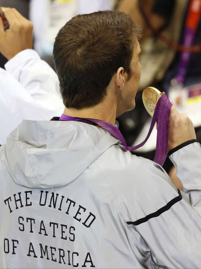 United States' Michael Phelps displays the gold medal he won in the men's 100-meter butterfly swimming final at the Aquatics Centre in the Olympic Park during the 2012 Summer Olympics in London, Friday, Aug. 3, 2012. (Julio Cortez / Associated Press)