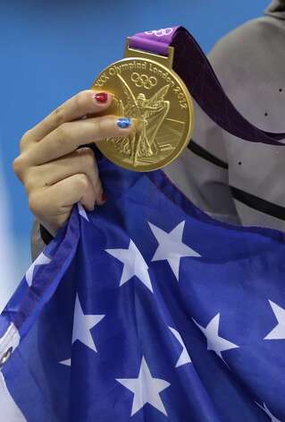 United States' Katie Ledecky holds her country's flag and displays her gold medals for the women's 800-meter freestyle swimming final at the Aquatics Centre in the Olympic Park during the 2012 Summer Olympics, London, Friday, Aug. 3, 2012.  (Matt Slocum / Associated Press)