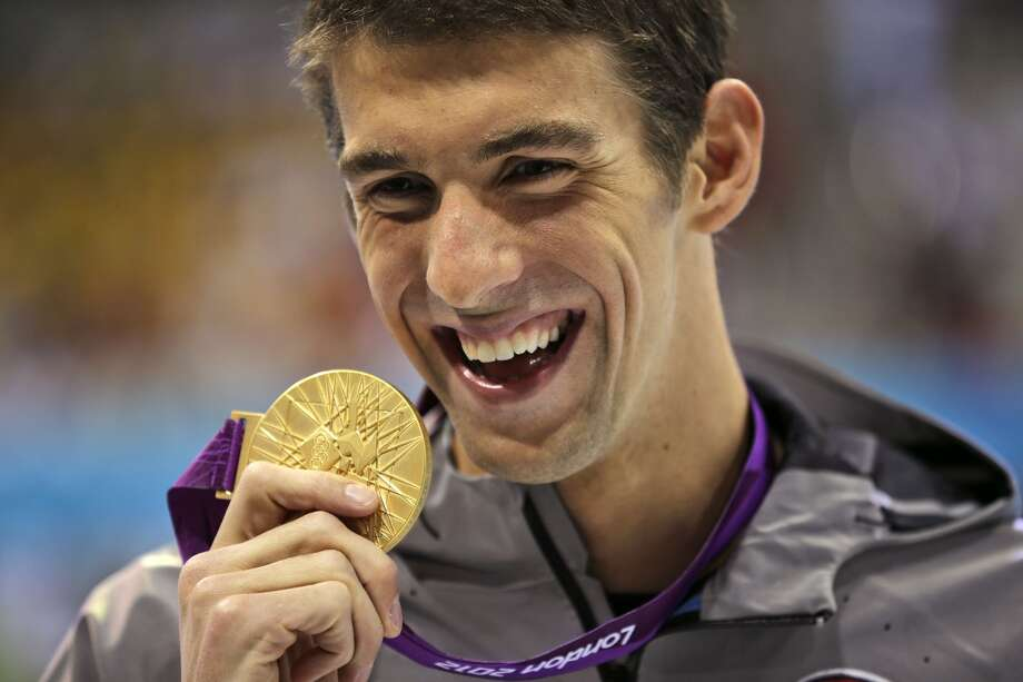 Michael Phelps displays his gold medal for the men's 100-meter butterfly swimming final at the Aquatics Centre in the Olympic Park during the 2012 Summer Olympics in London, Friday, Aug. 3, 2012.  (Matt Slocum / Associated Press)