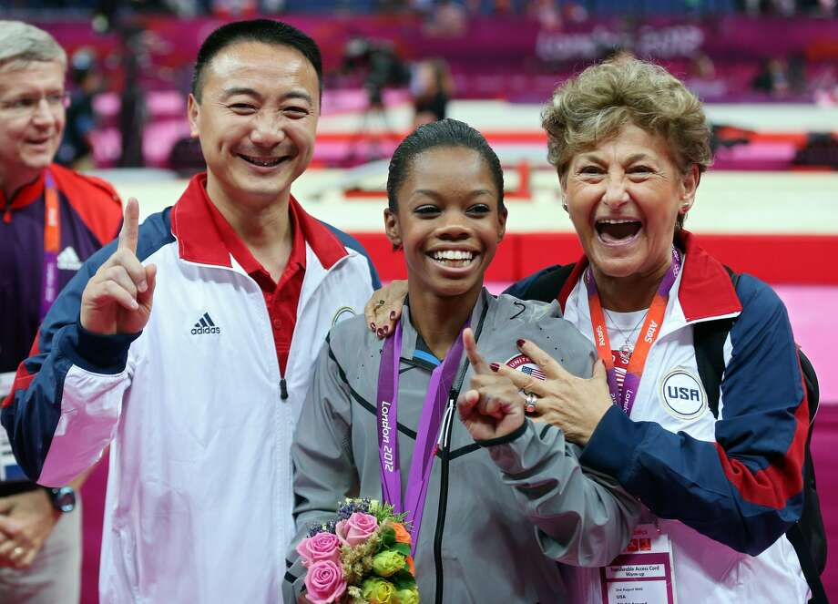 Gabrielle Douglas of the United States celebrates winning the gold medal with coach Liang Chow and team coordinator Martha Karolyi after the Artistic Gymnastics Women's Individual All-Around final on Day 6 of the London 2012 Olympic Games at North Greenwich Arena on August 2, 2012 in London, England.  (Streeter Lecka / Getty Images)