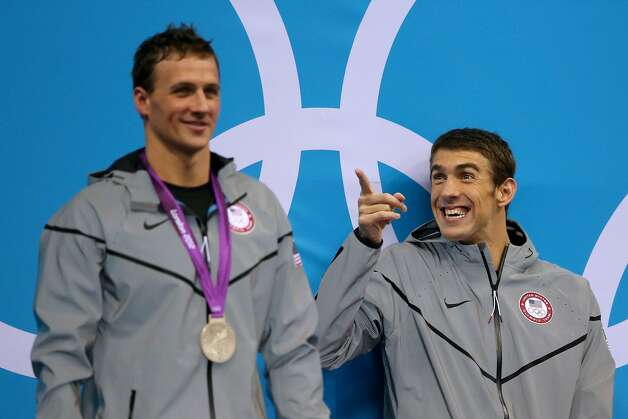 Gold medalist Michael Phelps reacts while waiting the receive his medal alongside silver medalist Ryan Lochte of the United States on the podium during the medal ceremony for the Men's 200m Individual Medley final on Day 6 of the London 2012 Olympic Games at the Aquatics Centre on August 2, 2012 in London, England.  (Ezra Shaw / Getty Images)