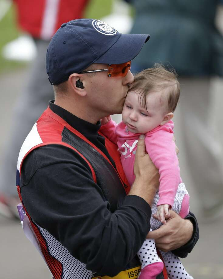 United States of America's Vincent Hancock kisses his 5-month-old daughter Brenlyn after winning the gold medal in the final of the men's skeet event at the 2012 Summer Olympics, Tuesday, July 31, 2012, in London.  (Rebecca Blackwell / Associated Press)
