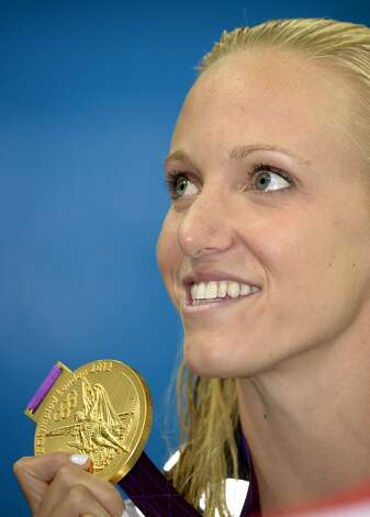 Cal alum Dana Vollmer poses with her gold medal for the women's 100-meter butterfly swimming final at the Aquatics Centre in the Olympic Park during the 2012 Summer Olympics in London, Sunday, July 29, 2012. Vollmer set a new world record with a time of 55.98.  (Mark J. Terrill / Associated Press)
