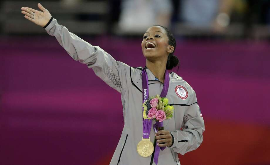 U.S. gymnast Gabrielle Douglas acknowledges the crowd after receiving her gold medal during the artistic gymnastics women's individual all-around competition at the 2012 Summer Olympics, Thursday, Aug. 2, 2012, in London.  (Gregory Bull / Associated Press)