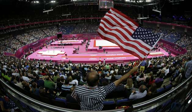 Rome Milan of Fort Worth, Texas, waves the U.S. flag during the Artistic Gymnastics men's qualification at the 2012 Summer Olympics, Saturday, July 28, 2012, in London.  (Julie Jacobson / Associated Press)