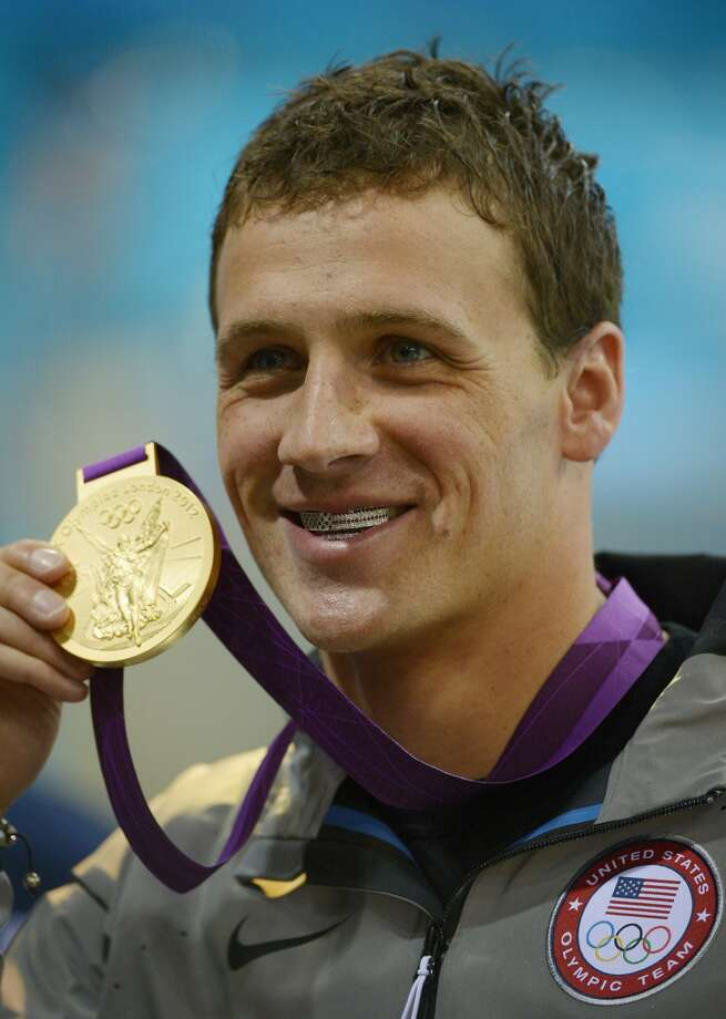 Ryan Lochte poses with his gold medal and patriotic grill for the men's 400-meter individual medley swimming final at the Aquatics Centre in the Olympic Park during the 2012 Summer Olympics in London, Saturday, July 28, 2012.  (Mark J. Terrill / Associated Press)