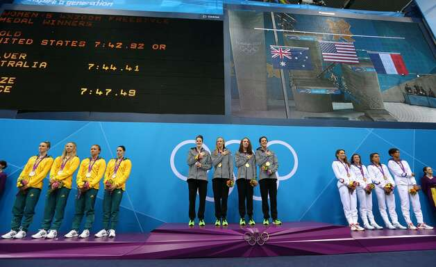 (L-R) SIlver medal winners team Australia, gold medal winners team United States and bronze medal winners team France stand on the podium during the medal ceremony for the Women's 4x200m Freestyle Relay on Day 5 of the London 2012 Olympic Games at the Aquatics Centre on August 1, 2012 in London, England. (Clive Rose / Getty Images)