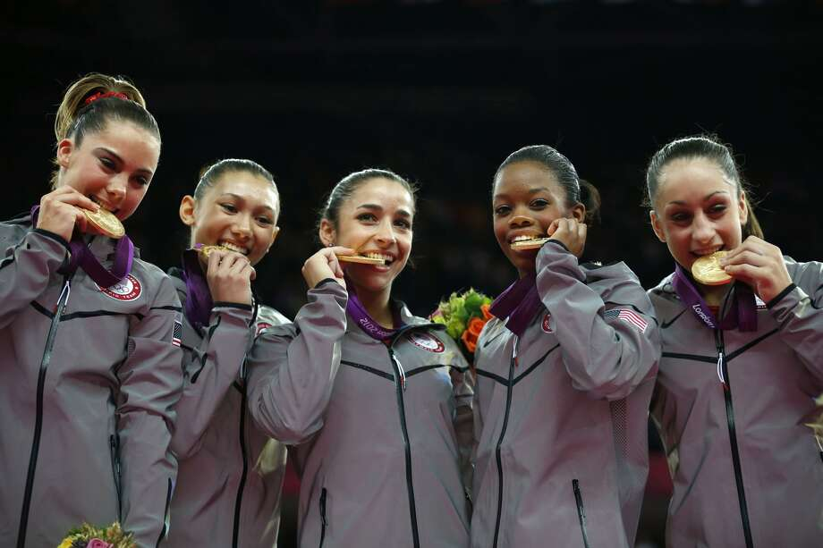 U.S. gymnast McKayla Maroney, Kyla Ross, Alexandra Raisman, Gabrielle Douglas and Jordyn Wieber bite their gold medals at the Artistic Gymnastics women's team final at the 2012 Summer Olympics, Tuesday, July 31, 2012, in London.  (Matt Dunham / Associated Press)