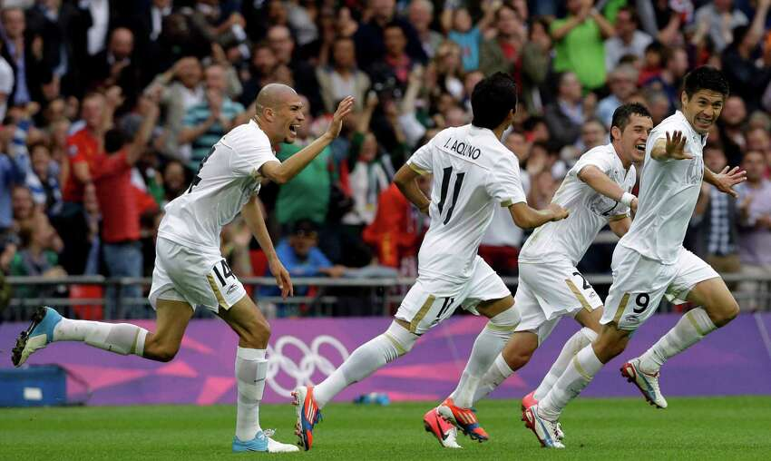 Mexico's Oribe Peralta (9) celebrates his goal with teammates Jorge Enriquez (14), Javier Aquino (11) and Israel Jimenez, second right, during their men's soccer semifinal match against Japan at Wembley Stadium during the 2012 Summer Olympics, Tuesday, Aug. 7, 2012, in London. (AP Photo/Luca Bruno)