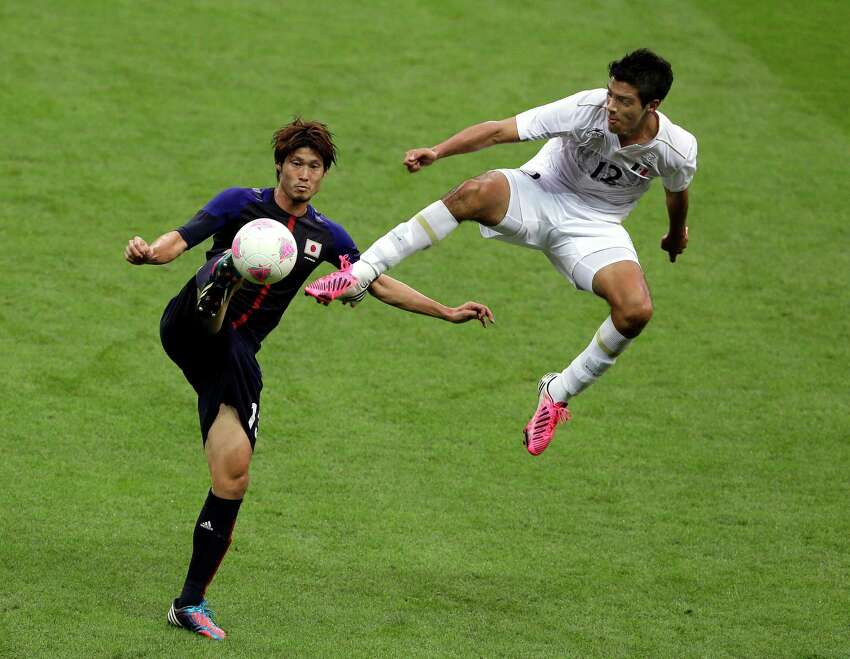 Mexico's Raul Jimenez, right, and Japan's Daisuke Suzuki vie for the ball during their semifinal soccer match at Wembley Stadium at the 2012 Summer Olympics, in London, Tuesday, Aug. 7, 2012. (AP Photo/Kirsty Wigglesworth)
