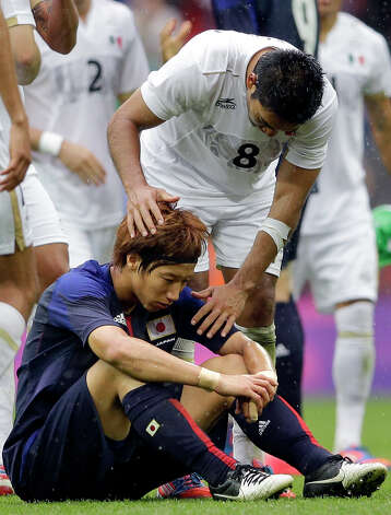 Mexico's Marco Fabian, top, talks to Japan's Yuki Otsu, bottom, at the end of their men's soccer semifinal match at Wembley Stadium at the 2012 Summer Olympics, Tuesday, Aug. 7, 2012, in London. Mexico won 3-1. (AP Photo/Victor R. Caivano) Photo: Victor R. Caivano, Associated Press / AP