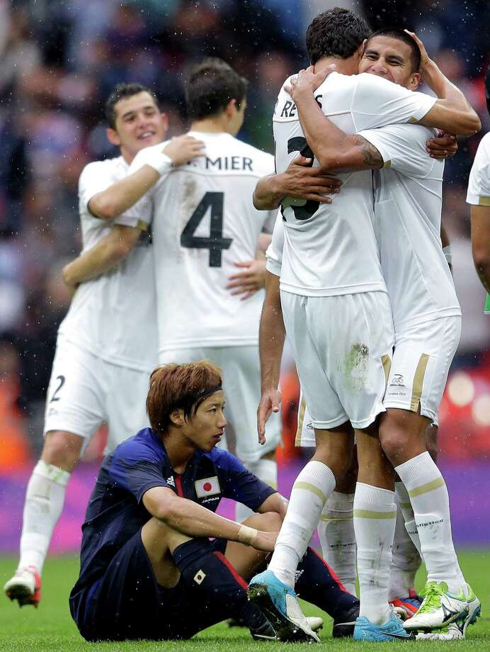 Japan's Yuki Otsu, bottom, sits on the ground as Mexico's Carlos Salcido, right, and teammate Diego Reyes, second right, hug at the end of their men's soccer semifinal match at Wembley Stadium at the 2012 Summer Olympics, Tuesday, Aug. 7, 2012, in London. (AP Photo/Victor R. Caivano) Photo: Victor R. Caivano, Associated Press / AP