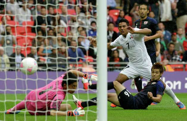 Mexico's Javier Cortes, center, scores past by Japan's Shuichi Gonda during the men's soccer semifinal match between Japan and Mexico at Wembley Stadium, at the 2012 Summer Olympics, Tuesday, Aug. 7, 2012, in London. (AP Photo/Luca Bruno) Photo: Luca Bruno, Associated Press / AP