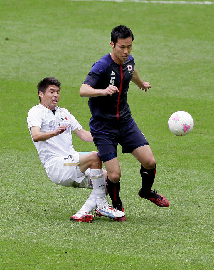 Mexico's Oribe Peralta, left, and Japan's Maya Yoshida vie for the ball during their semifinal soccer match at Wembley Stadium at the 2012 Summer Olympics, in London, Tuesday, Aug. 7, 2012. (AP Photo/Kirsty Wigglesworth) Photo: Kirsty Wigglesworth, Associated Press / AP
