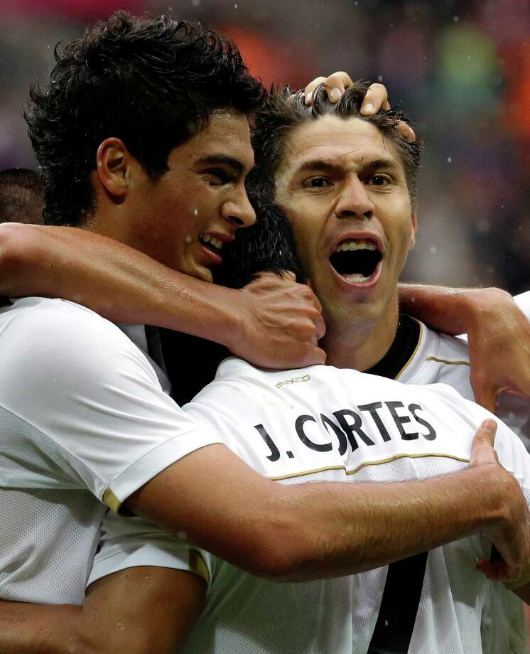 Mexico's Javier Cortes (7) celebrates his goal with teammates Mexico's Raul Jimenez, left and Mexico's Oribe Peralta during the men's soccer semifinal match against Japan at Wembley Stadium,at the 2012 Summer Olympics, Tuesday, Aug. 7, 2012 in London. (AP Photo/Luca Bruno) Photo: Luca Bruno, Associated Press / AP