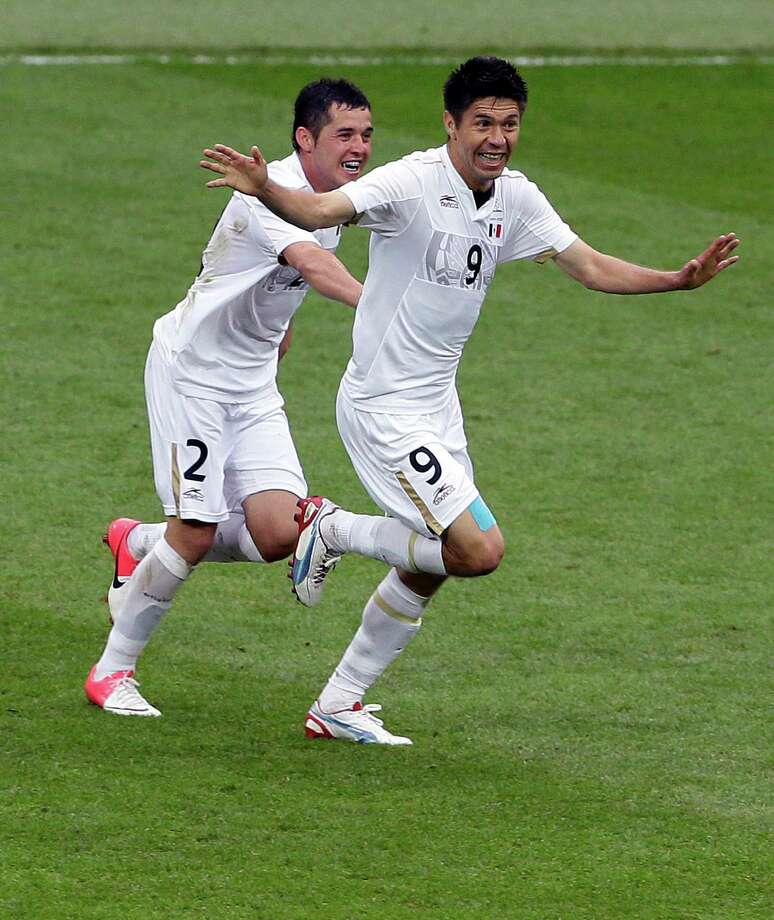 Mexico's Oribe Peralta, right, celebrates with Israel Jimenez after scoring against Japan during their semifinal soccer match at Wembley Stadium at the 2012 Summer Olympics, in London, Tuesday, Aug. 7, 2012. (AP Photo/Kirsty Wigglesworth) Photo: Kirsty Wigglesworth, Associated Press / AP