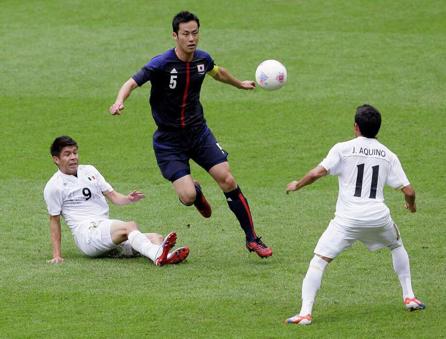 Japan's Maya Yoshida, center, vies for the ball with Mexico's Oribe Peralta, left, and Javier Aquino, right, during their semifinal soccer match at Wembley Stadium at the 2012 Summer Olympics, in London, Tuesday, Aug. 7, 2012. (AP Photo/Kirsty Wigglesworth) Photo: Kirsty Wigglesworth, Associated Press / AP