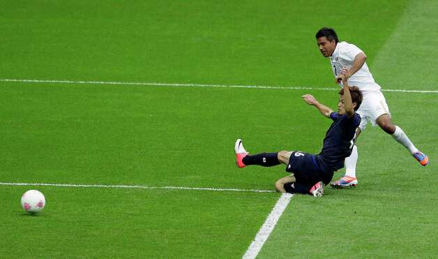 Mexico's Javier Cortes scores past Japan's Hotaru Yamaguchi during their men's semifinal soccer match at Wembley Stadium at the 2012 Summer Olympics in London, Tuesday, Aug. 7, 2012. (AP Photo/Kirsty Wigglesworth) Photo: Kirsty Wigglesworth, Associated Press / AP