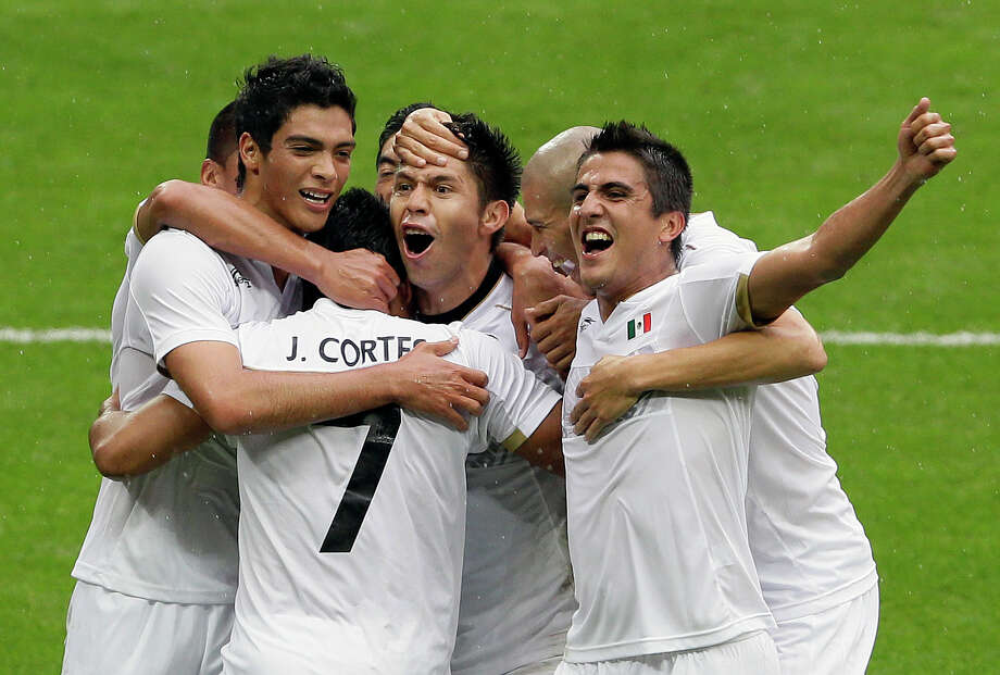 Mexico's Javier Cortes (7) is hugged by his teammates after scoring against Japan in during their semifinal soccer match at Wembley Stadium at the 2012 Summer Olympics, London, Tuesday, Aug. 7, 2012. (AP Photo/Kirsty Wigglesworth) Photo: Kirsty Wigglesworth, Associated Press / AP
