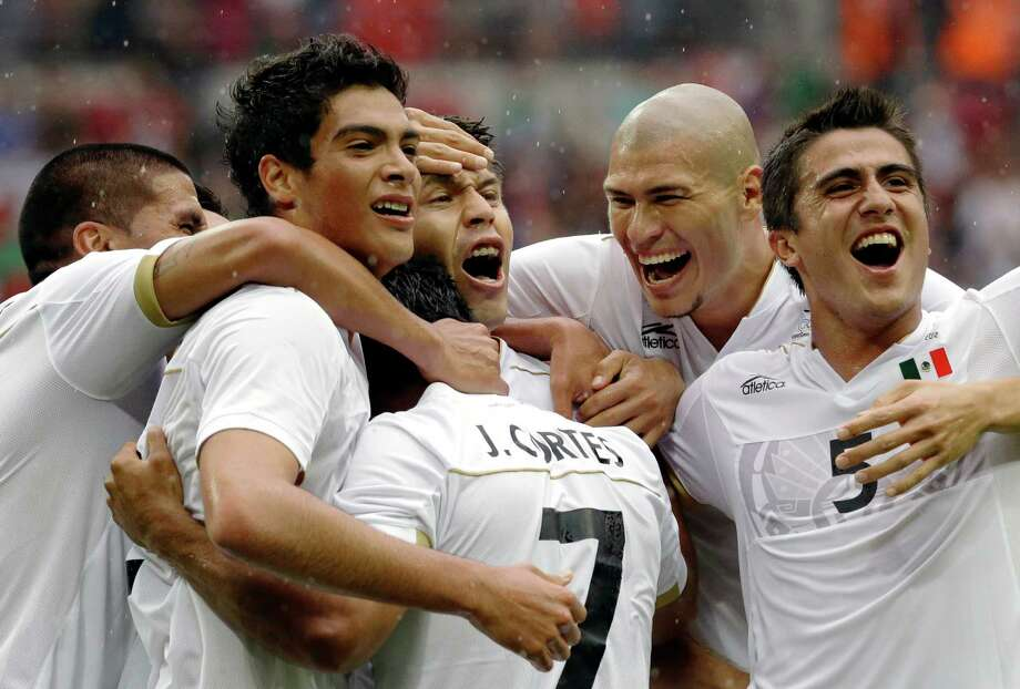 Mexico's Javier Cortes, (7) celebrates with his teammates Raul Jimenez, left, Oribe Peralta, Jorge Enriquez and Darvin Chavez, right, after scoring during the men's soccer semifinal match between Japan and Mexico at Wembley Stadium, at the 2012 Summer Olympics, Tuesday, Aug. 7, 2012, in London. (AP Photo/Luca Bruno) Photo: Luca Bruno, Associated Press / AP