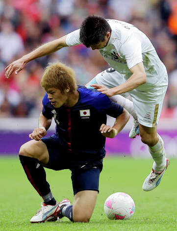 Mexico's Oribe Peralta, top, battles for the ball against Japan's Hiroki Sakai during their men's soccer semifinal match at Wembley Stadium at the 2012 Summer Olympics, Tuesday, Aug. 7, 2012, in London.  (AP Photo/Victor R. Caivano) Photo: Victor R. Caivano, Associated Press / AP