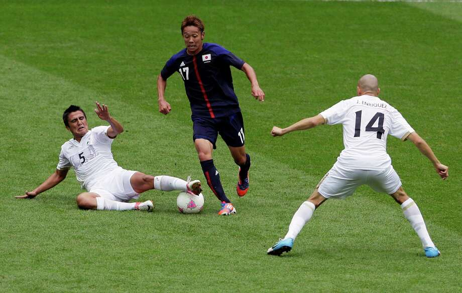 Japan's Hiroshi Kiyotake, center, vies for the ball with Mexico's Darvin Chavez, left, and Jorge Enriquez, right, during their semifinal soccer match at Wembley Stadium at the 2012 Summer Olympics, London, Tuesday, Aug. 7, 2012. (AP Photo/Kirsty Wigglesworth) Photo: Kirsty Wigglesworth, Associated Press / AP