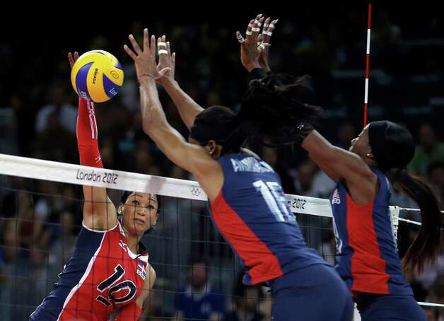 Dominican Republic's Milagros Cabral de la Cruz, left, spikes the ball past United States' Foluke Akinradewo, center, and Destinee Hooker during a women's quarterfinal volleyball match at the 2012 Summer Olympics, Tuesday, Aug. 7, 2012, in London. (AP Photo/Jeff Roberson) Photo: Jeff Roberson, Associated Press / AP
