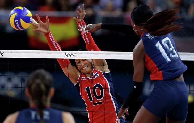 United States' Destinee Hooker, right, spikes the ball past Dominican Republic's Milagros Cabral de la Cruz during a women's quarterfinal volleyball match at the 2012 Summer Olympics, Tuesday, Aug. 7, 2012, in London. (AP Photo/Jeff Roberson) Photo: Jeff Roberson, Associated Press / AP