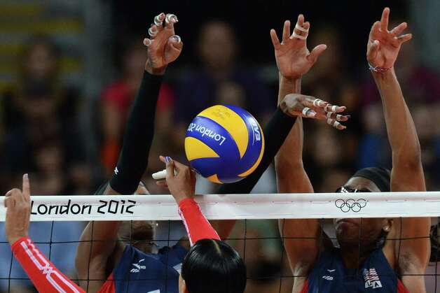 Dominican Republic's Milagros Cabral De La Cruz (C) spikes as Destinee Hooker (L) and Foluke Akinradewo of the US attempt to block during the Women's quarterfinal volleyball match between the US and Dominican Republic in the 2012 London Olympic Games in London on August 7, 2012. AFP PHOTO/KIRILL KUDRYAVTSEVKIRILL KUDRYAVTSEV/AFP/GettyImages Photo: KIRILL KUDRYAVTSEV, AFP/Getty Images / AFP
