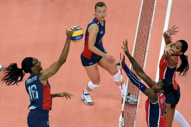 US' Foluke Akinradewo (L) spikes during the Women's quarterfinal volleyball match between the USA and the Dominican Republic in the 2012 London Olympic Games in London on August 7, 2012. AFP PHOTO / KIRILL KUDRYAVTSEVKIRILL KUDRYAVTSEV/AFP/GettyImages Photo: KIRILL KUDRYAVTSEV, AFP/Getty Images / AFP