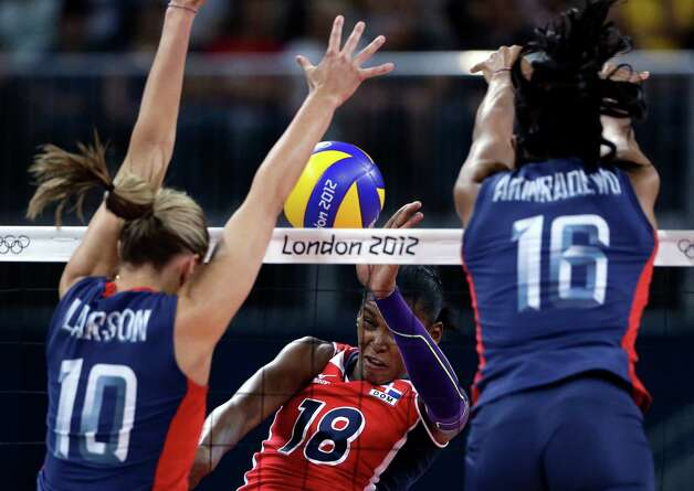 United States' Jordan Larson, left, and Foluke Akinradewo, right, block a spike from Dominican Republic's Bethania de la Cruz de Pena during a women's quarterfinal volleyball match at the 2012 Summer Olympics, Tuesday, Aug. 7, 2012, in London. (AP Photo/Jeff Roberson) Photo: Jeff Roberson, Associated Press / AP