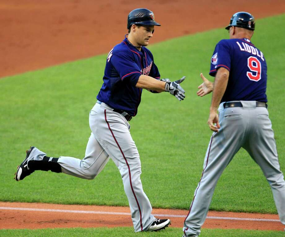 Minnesota Twins' Josh Willingham, left, is congratulated by third base coach Steve Liddle after Willingham hit a solo home run off Cleveland Indians starting pitcher Zach McAllister in the second inning of a baseball game, Monday, Aug. 6, 2012, in Cleveland. (AP Photo/Tony Dejak) Photo: Tony Dejak
