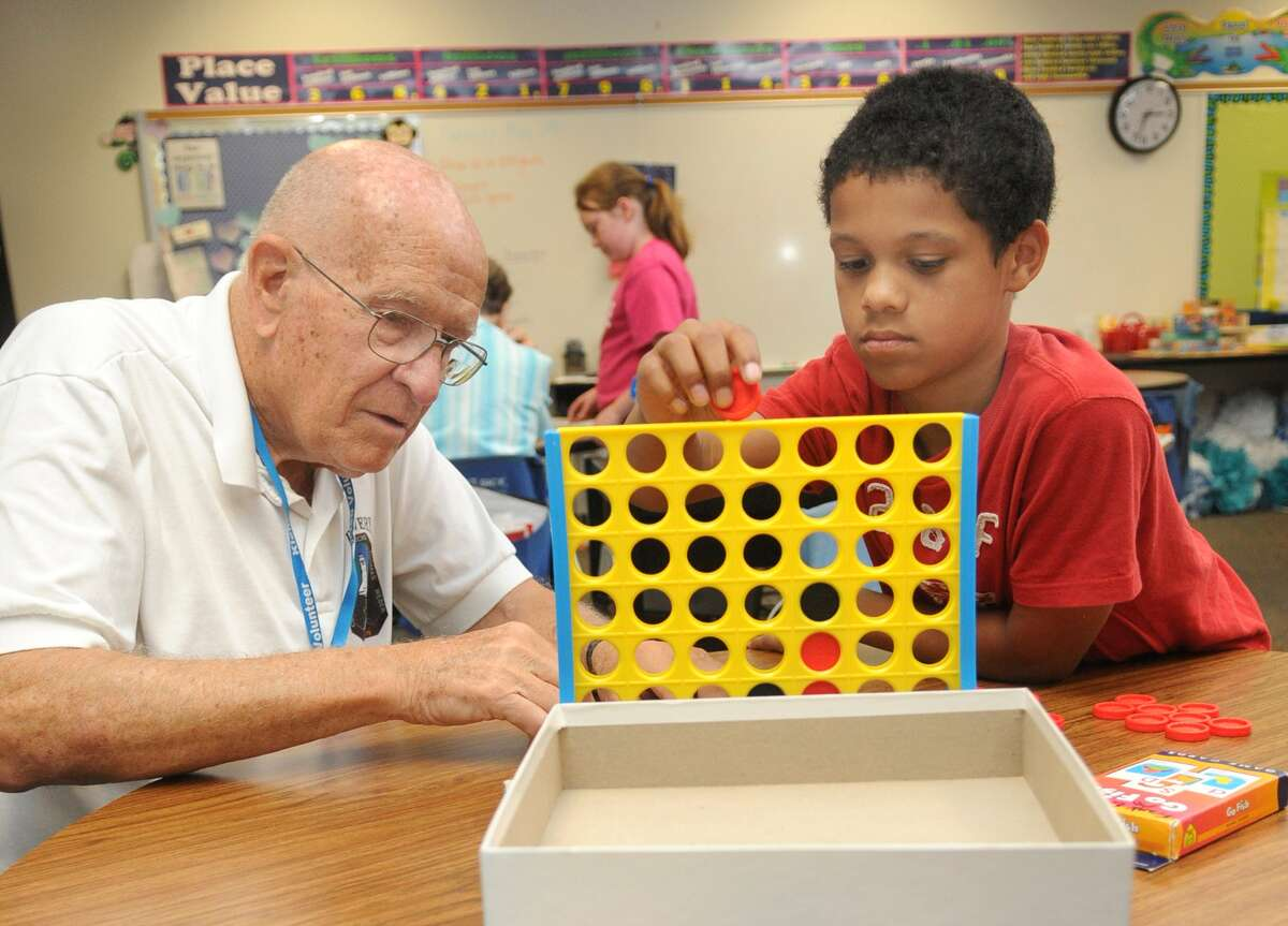 Richard Kregel, 80, left, plays a game of Connect Four with third-grader Caleb Bell, 8, during a Grand Pals mentoring session at Frank Elementary in Spring.