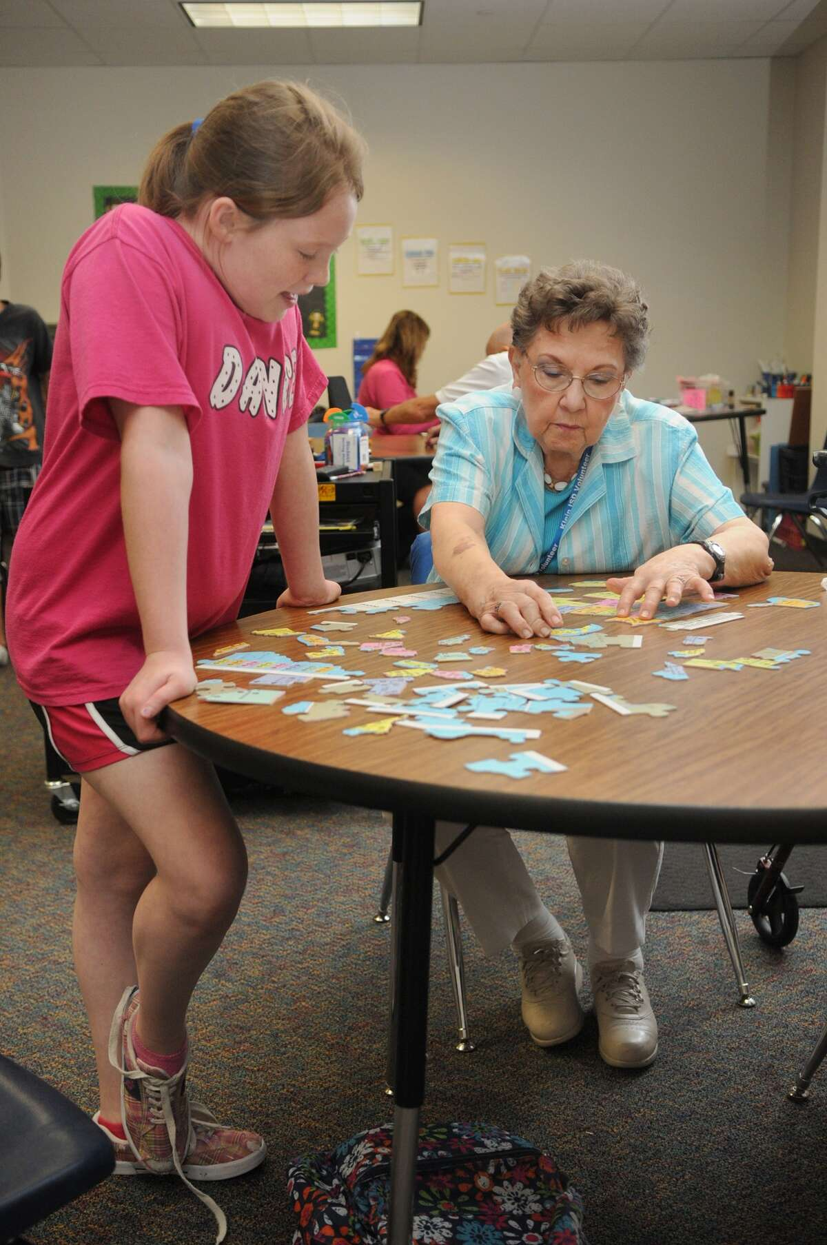 Natalie Soph, 9, from left, a fourth-grader, and Ellen Curfman, 82, team-up on a puzzle of the United States during their Grand Pals mentoring session at Frank Elementary in Spring.