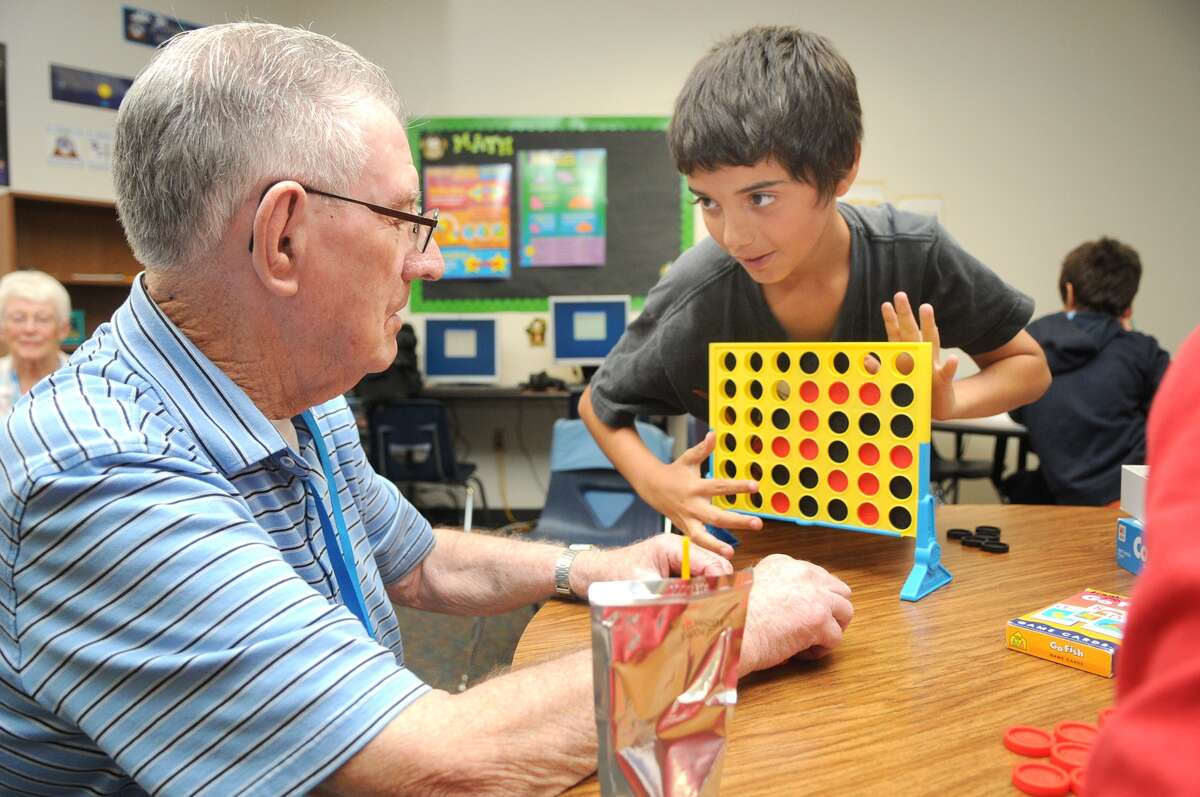 George Fiscella, 86, left, plays a game of Connect Four with fifth-grader Anthony Arroyo, 11, during a Grand Pals mentoring session at Frank Elementary in Spring.