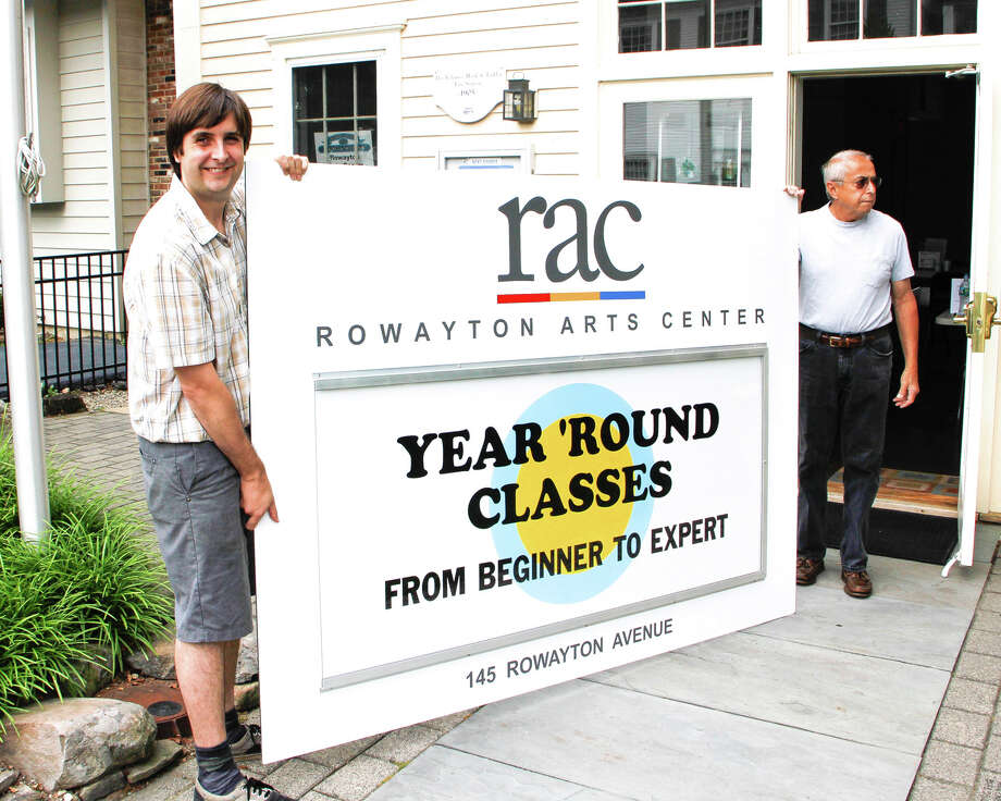Rowayton Arts Center Board Member Bruce Horan, left, helps Toni Masi of Norwalk Signs deliver RAC's new sign for installation on the Rowayton community fence. Check it out for class information as well as info promoting RAC events. Photo: Contributed Photo / Norwalk Citizen