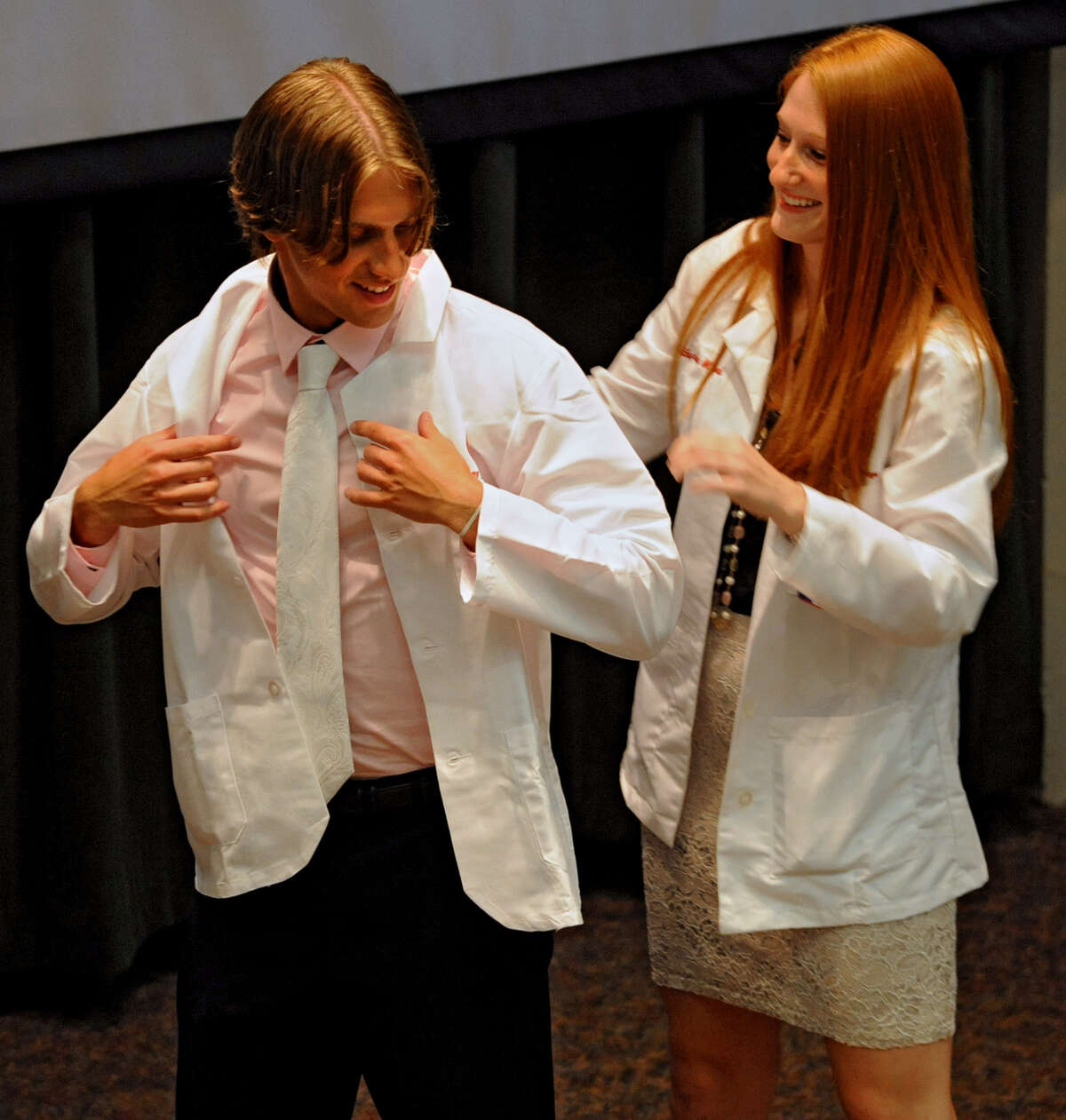 Albany Medical College student Stevan Pupovac of Saratoga receives his first white coat from second year medical student Katie Medford of Clifton Park Tuesday, Aug. 7, 2012 in Albany, N.Y. Albany Medical College?s first-year medical students are initiated into the medical community by receiving their first white medical coat and by reciting the Hippocratic Oath. (Lori Van Buren / Times Union)