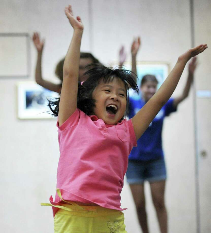 "Emily Chan, 7, leaps while dancing to ""We Go Together,"" a song from ""Grease,"" during a free workshop taught by dance instructor Jennifer Stanley of Gotta Dance, of Waterford at the William K. Sanford Town Library on Tuesday Aug. 7, 2012 in Colonie, NY.   (Philip Kamrass / Times Union) Photo: Philip Kamrass / 00018751A"