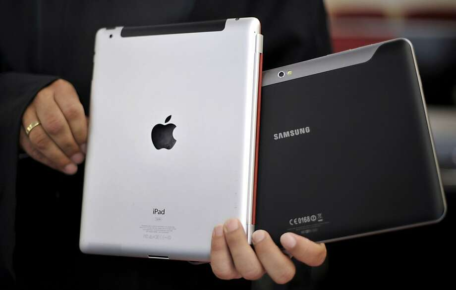 FILE - In this Aug. 25, 2011 file photo, an attorney holds an Apple iPad, left, and a Samsung Galaxy Tab 10.1 at the regional court in Duesseldorf, Germany. The two tech Titans will square off in federal court Monday, July 30, 2012, in a closely watched trial over control of the U.S. smart phone and computer tablet markets. Apple Inc. filed a lawsuit against Samsung Electronics Co. last year alleging the world's largest technology company's smartphones and computer tablets are illegal knockoffs of its popular iPhone and iPad products. (AP Photo/dapd, Sascha Schuermann, File) Photo: Sascha Schuermann, Associated Press