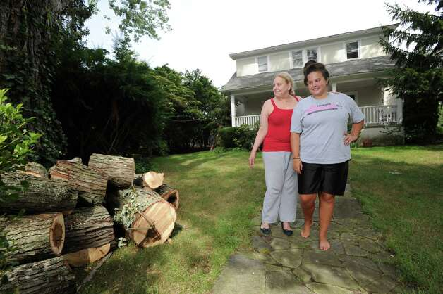 Barbara Cooper, left, and her daughter Elizabeth, inspect cut tree limbs in front of their Grimes Road home in Old Greenwich, Tuesday afternoon, Aug. 7, 2012. Cooper said tree limbs knocked down during the storm that hit Greenwich on Sunday fell on the power lines, causing a loss of electricity to their home for nearly two days. Photo: Bob Luckey / Greenwich Time