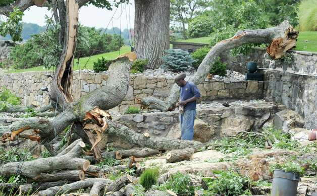 Derrick Dickens of D.L. Tree Service removes tree limbs knocked down by the storm that hit Greenwich Sunday night from a beach at the end Pilot Rock Lane in Riverside, Tuesday afternoon, Aug. 7, 2012. Photo: Bob Luckey / Greenwich Time
