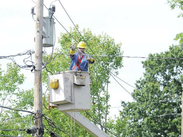 A lineman works to restore electricity to Barbara Cooper's home on Grimes Road in Old Greenwich Tuesday afternoon, Aug. 7, 2012. Cooper said tree limbs knocked down during the storm that hit Greenwich on Sunday fell on the power lines, causing a loss of electricity to their home for nearly two days. Photo: Bob Luckey / Greenwich Time