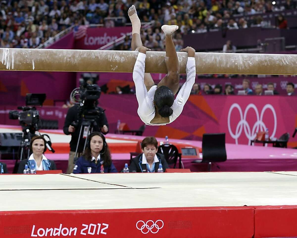 U.S. gymnast Gabrielle Douglas loses her balance and hangs onto the balance beam during the artistic gymnastics women's apparatus finals at the 2012 Summer Olympics, Tuesday, Aug. 7, 2012, in London. (AP Photo/Julie Jacobson)