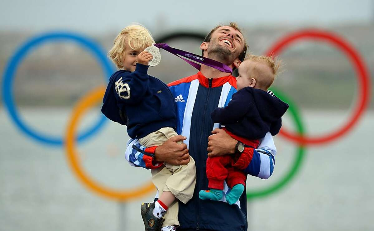 TOPSHOTS Britain's Nick Dempsey (C) poses with his sons Thomas-Flynn (L) and Oscar (R) after he won silver in the men's RS:X sailing class at the London 2012 Olympic Games, in Weymouth on August 7, 2012. AFP PHOTO/William WESTWILLIAM WEST/AFP/GettyImages