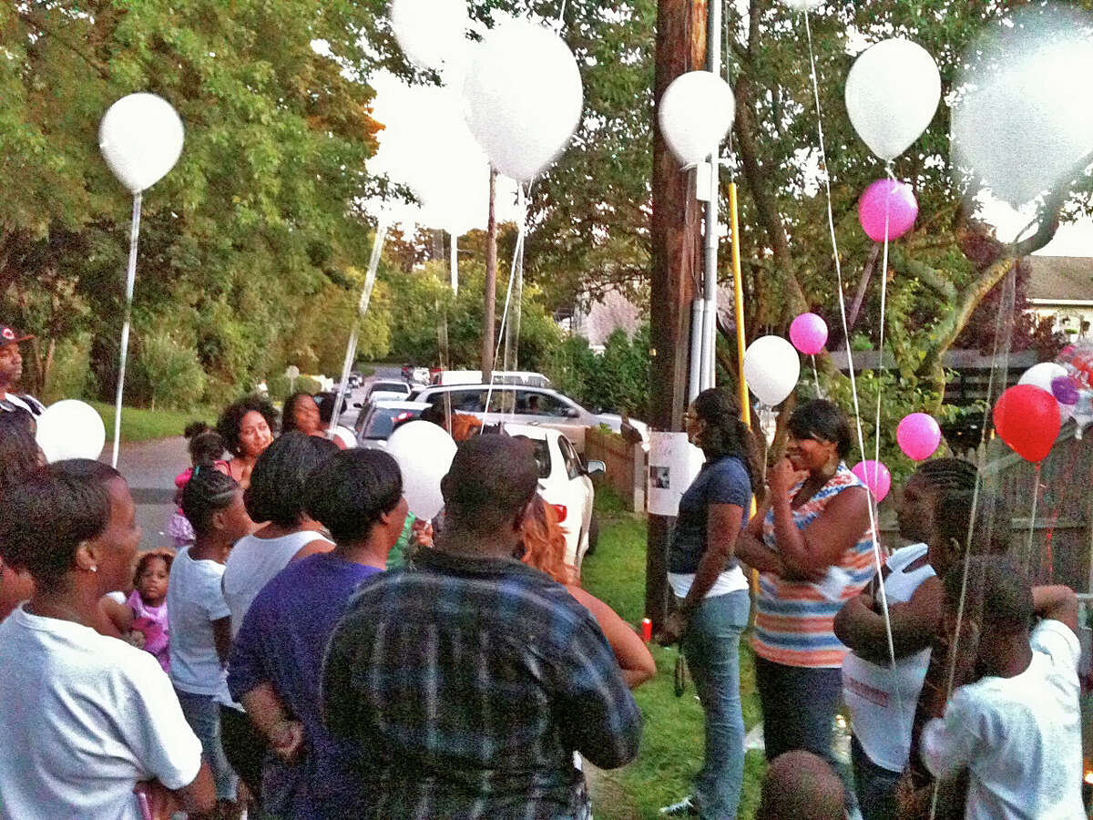 Friends and family members prepare to release pink and white balloons into the air in memory of Rickita Smalls and Iroquois Alston, who were shot to death a year ago Monday in Norwalk, during a remembrance ceremony held a the site of the crime.