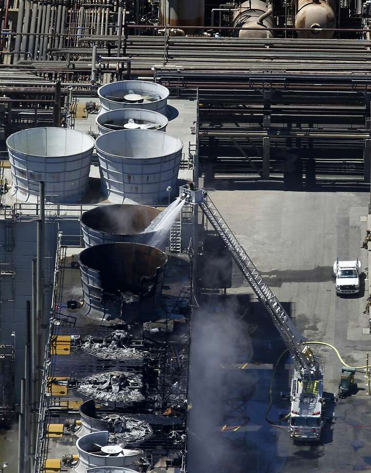 A fire truck continues to pour water on the No. 4 Crude Unit at the Chevron Refinery in Richmond, Calif. on Tuesday, Aug. 7, 2012, one day after an explosion and fire rocked the area and sent a giant plume of black smoke into the atmosphere. Photo: Paul Chinn, The Chronicle