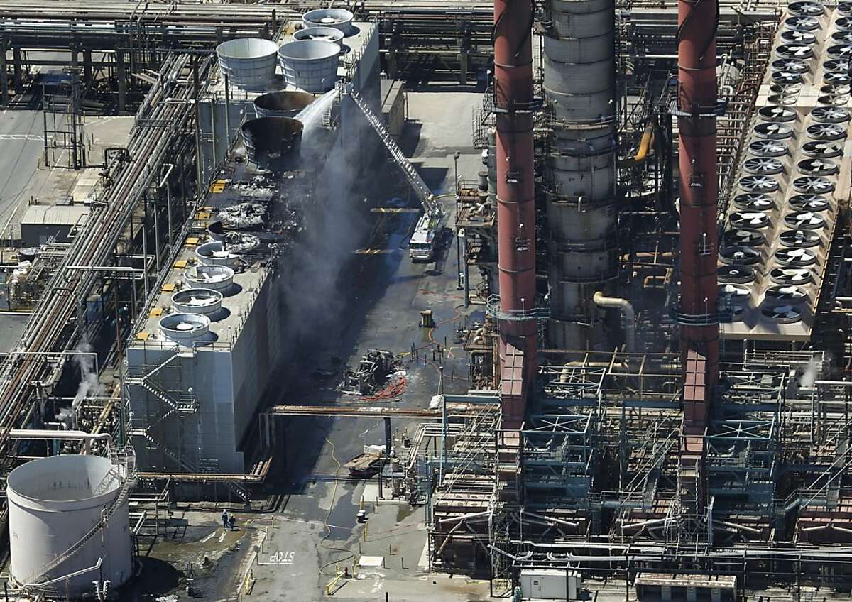 A fire truck continues to pour water on the No. 4 Crude Unit at the Chevron Refinery in Richmond, Calif. on Tuesday, Aug. 7, 2012, one day after an explosion and fire rocked the area and sent a giant plume of black smoke into the atmosphere.