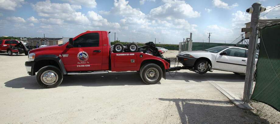A Bexar Towing truck pulls a car on it's lot.  John D. DeLoach, former owner now employee of Bexar Towing, was arrested Friday Aug. 3 for not lowering the company's towing charges to the city's mandated $85.  Tuesday, Aug. 7, 2012. Photo: BOB OWEN, San Antonio Express-News / © 2012 San Antonio Express-News