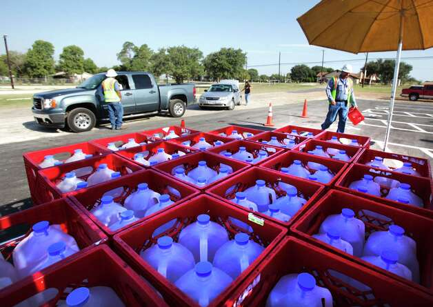 Crates of water are shaded by a large umbrella as SAWS workers hand out four gallons to residents of Somerset, where a gas line and water line were broken at a construction site.  Tuesday, Aug. 7, 2012. Photo: BOB OWEN, San Antonio Express-News / © 2012 San Antonio Express-News